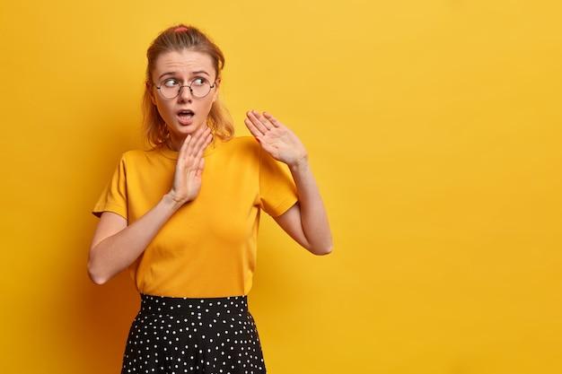 Verbaasd bang europees meisje houdt handpalmen naar voren vraagt om niet dichtbij te komen zegt blijf bij me weg, bang voor iets