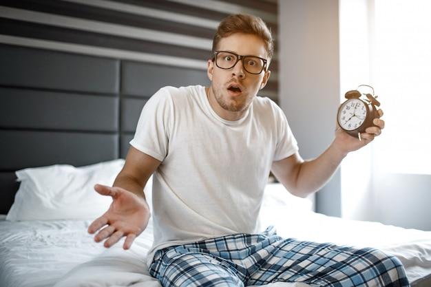 Verbaasd bang jonge man op bed vanmorgen. hij kijkt op de camera en houdt de klok vast. hij heeft zich verslapen.