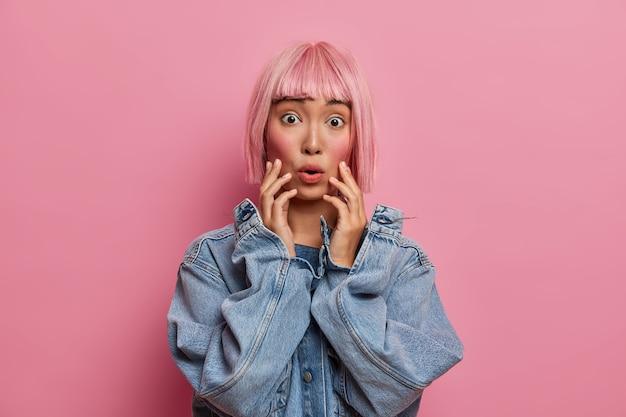 Verbaasd bange geschrokken aziatische vrouw grijpt gezicht en staart, heeft kort roze haar, ergens bang voor, hijgt naar adem van angst, is getuige van een vreselijk ongeluk, draagt een oversized spijkerjack.