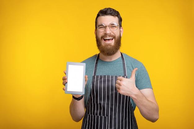 Verbaasd bebaarde chef-kok tablet houden en duimen opdagen