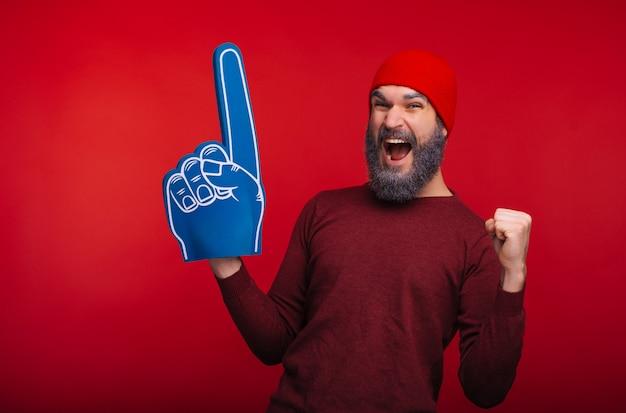 Verbaasd bebaarde hipster man permanent over rode ruimte en het vieren van succes met fan vinger handschoen