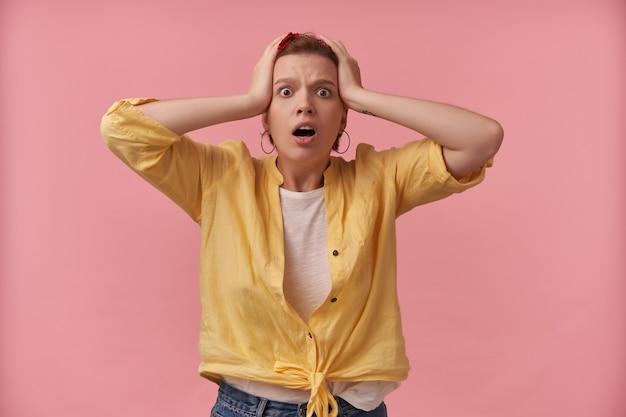 Verbaasd bezorgd jonge vrouw in geel overhemd met hoofdband en handen op het hoofd kijkt geschokt en schreeuwend over roze muur