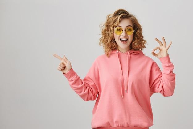 Verbaasd blij meisje dat naar links wijst, productadvertentie aanbevelen, ok gebaar maken