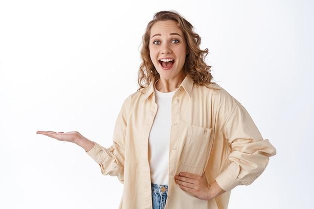 Verbaasd blond meisje naar adem snakkend en zeggend wow, je logo of product in de hand houdend, weergeven op palm, staande over een witte muur