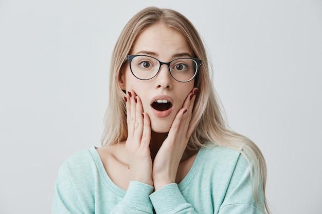 Verbaasd blond vrouwelijk model met bril houdt mond wijd open, kijkt verbaasd, houdt handen op wang, herinnert zich een belangrijke plicht die ze onmiddellijk moet doen. shock en ongeloof concept