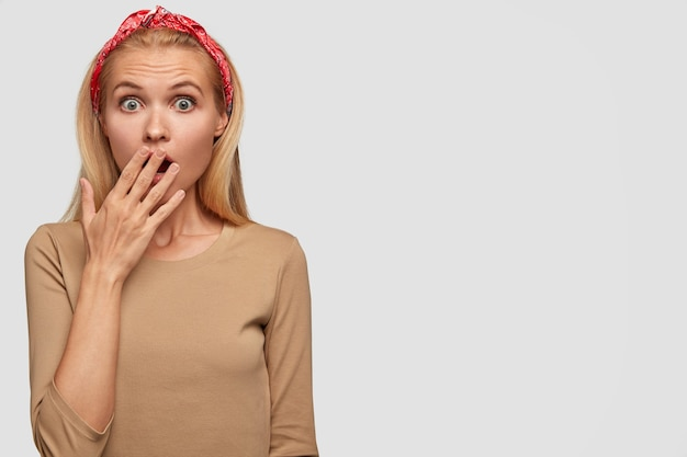 Verbaasd blonde vrouw met verbaasde uitdrukking, staart met afgeluisterde ogen, sluit mond