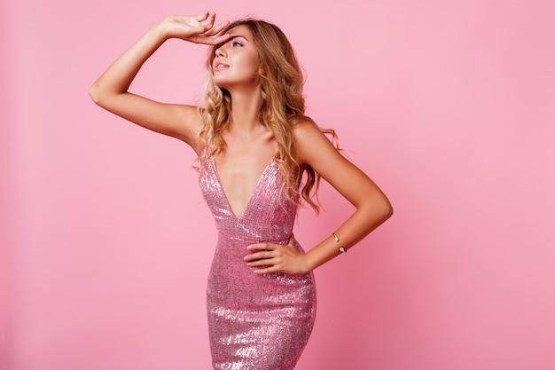 Verbaasd blonde vrouw met winderige haren poseren. roze muur. prachtig model. extatische emoties.