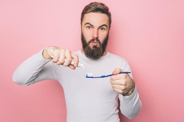 Verbaasd brengt wat tandpasta op een tandenborstel