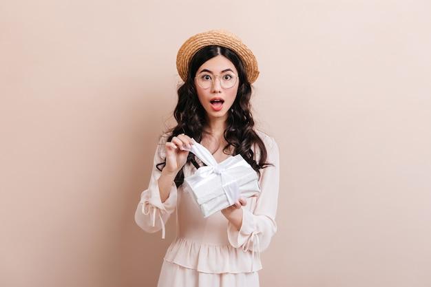 Verbaasd chinees vrouwen openingsgift. studio die van verraste aziatische vrouw met verjaardagsgeschenk is ontsproten.