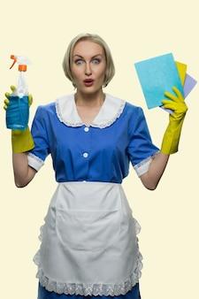 Verbaasd dienstmeisje met vloerkleden en wasmiddel