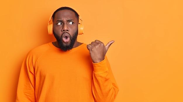 Verbaasd donkere huid afro-amerikaanse man met dikke baard wijst duim weg op lege ruimte