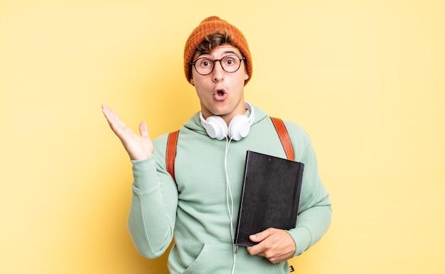Verbaasd en geschokt kijkend, met open mond een object vasthoudend met een open hand aan de zijkant. studentenconcept