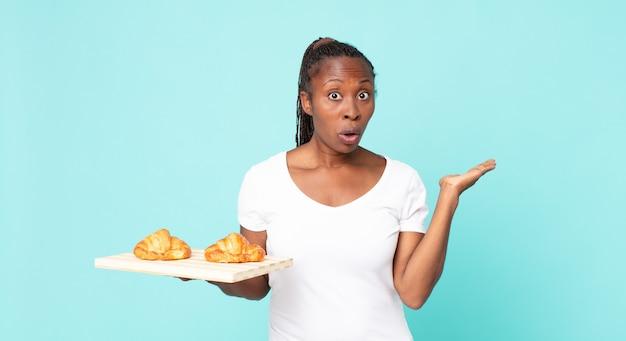 Verbaasd en geschokt kijkend, met open mond terwijl je een voorwerp vasthoudt en een croissantblad vasthoudt