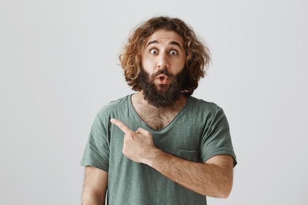 Verbaasd en onder de indruk van een man met een baard uit het midden-oosten, wijzende vinger naar links, zeggend wow