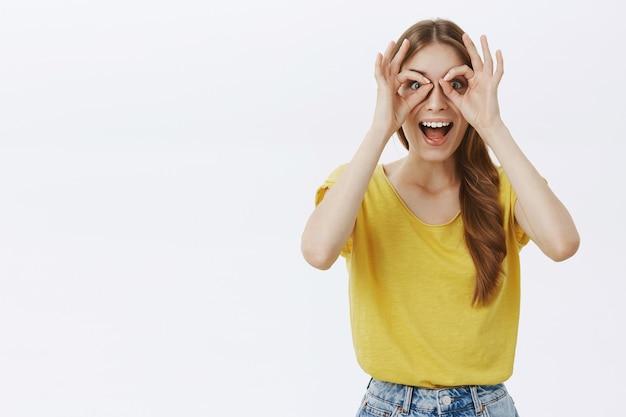 Verbaasd en opgewonden meisje dat door geamuseerd handbril kijkt