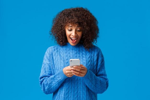 Verbaasd en verrast, gelukkig emotionele afro-amerikaanse vrouw juichen en schreeuwen