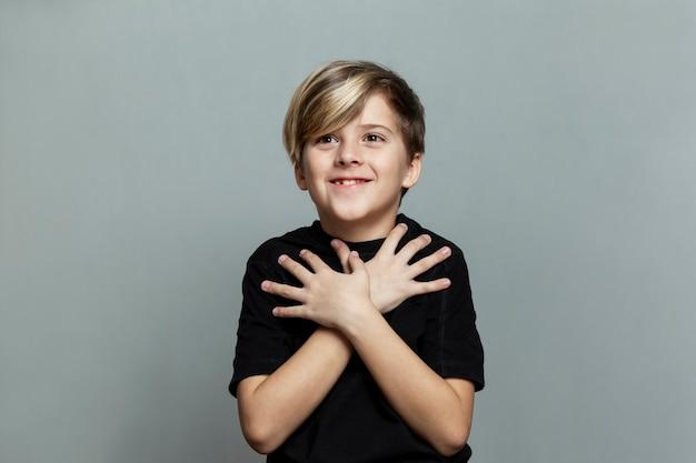 Verbaasd en verrast lachende jongen met een modieus kapsel in een zwart t-shirt