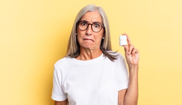 Verbaasd en verward kijken, lip bijten met een nerveus gebaar, het antwoord op het probleem niet weten en een pillenfles vasthouden