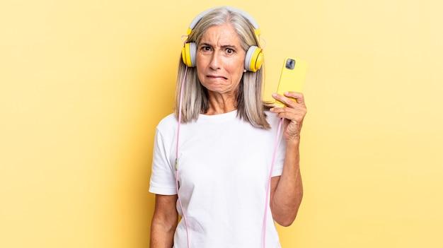 Verbaasd en verward kijken, lip bijten met een nerveus gebaar, niet wetend het antwoord op het probleem met een koptelefoon