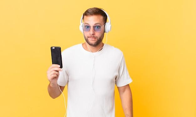 Verbaasd en verward kijken, muziek luisteren met een koptelefoon en een smartphone