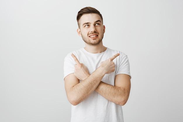 Verbaasd en verward knappe kerel wijzende vingers zijwaarts, geconfronteerd met moeilijke keuze
