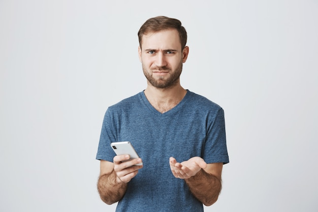 Verbaasd en verward man schouderophalend na het lezen van bericht op de telefoon