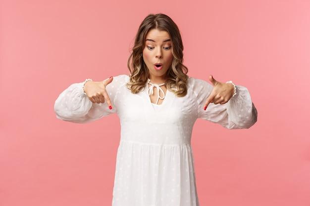 Verbaasd en verwonderd goed uitziende blonde europese vrouw 20s, draag een prachtige witte jurk, kijkend en wijzend, in paniek over iets geweldigs en adembenemend, roze muur.