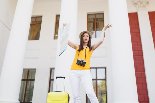 Verbaasd geïrriteerde reiziger toeristische vrouw in hoed met koffer en retro vintage fotocamera spreidende handen houden stadsplattegrond buiten. meisje op weekendje weg naar het buitenland. toeristische reis levensstijl.