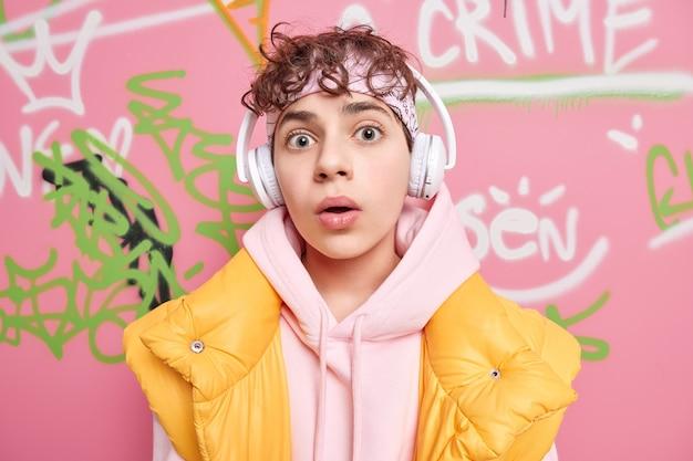 Verbaasd gekrulde harige hipster man kijkt met verwondering naar camera luistert muziek via draadloze koptelefoon gekleed in sweatshirt en vest vormt tegen kleurrijke graffiti muur