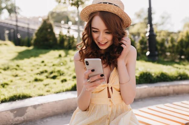 Verbaasd gember jonge vrouw gelezen telefoonbericht in park. outdoor portret van mooie elegante meisje in gele jurk zittend op een bankje met smartphone.