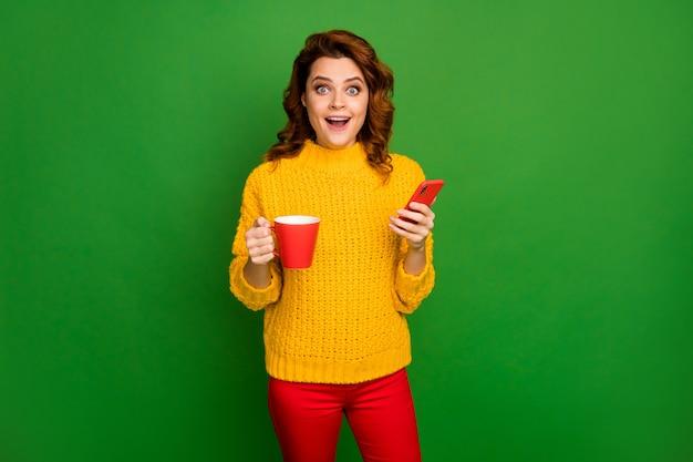 Verbaasd geschokt gek vrouw rust ontspannen houden mok heet cafeïne drank gebruik smartphone onder de indruk volgelingen schreeuwen slijtage trui trui broek broek geïsoleerd heldere glans kleur muur