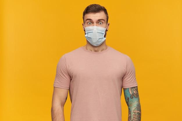 Verbaasd geschokt getatoeëerde jongeman in roze t-shirt en hygiënisch masker om infectie met baard te voorkomen kijkt verbaasd en kijkt naar voorkant over gele muur