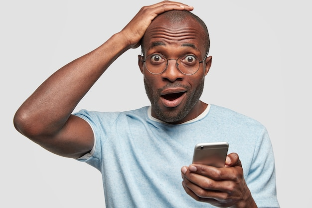 Verbaasd geschokt jongeman ontvangt berichtherinnering op slimme telefoon, vergeet belangrijke vergadering