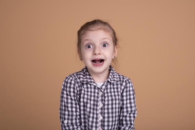 Verbaasd geschokt meisje met open mond dat op beige neutrale muur wordt geïsoleerd