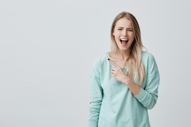 Verbaasd geschokt vrouwelijk model met recht blond haar, gekleed in blauwe kleding, poseren met wijd geopende mond, wijzend met wijsvinger op kopie ruimte