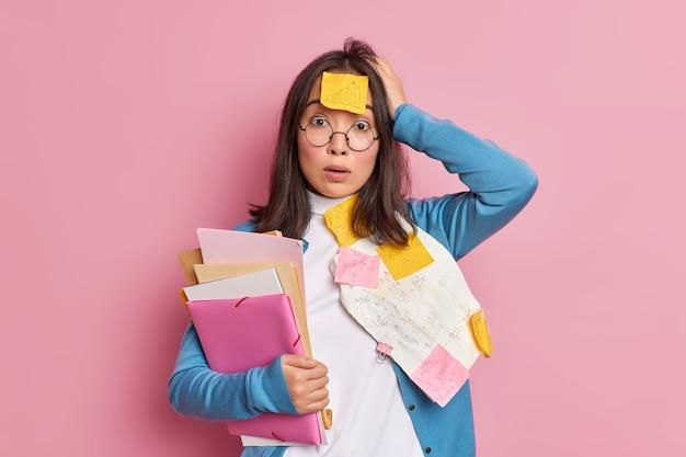 Verbaasd geschokt vrouwelijke kantoormedewerker overladen met papierwerk verbijsterd om deadline te hebben voor het afronden van onderzoek houdt mappen vast houdt hand op hoofd draagt ronde bril.