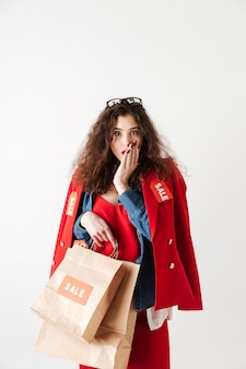 Verbaasd geschokt winkelen verkoop vrouw met papieren boodschappentassen
