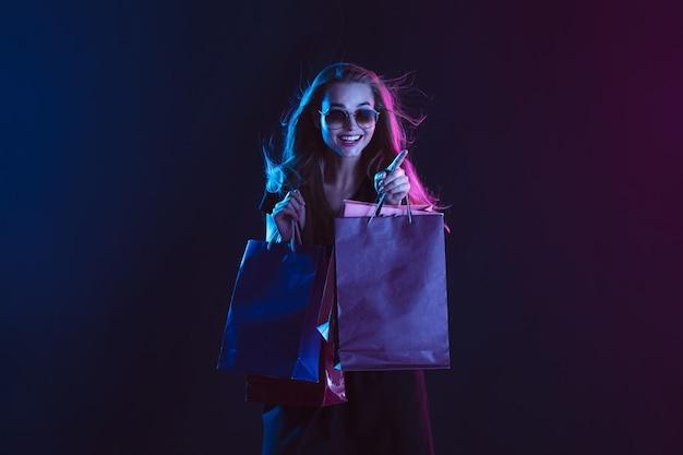 Verbaasd, geschrokken van boodschappentassen, vrolijk. portret van een jonge vrouw in neonlicht op donkere achtergrondkleur. de menselijke emoties, zwarte vrijdag, cybermaandag, aankopen, verkoop, financieel concept.