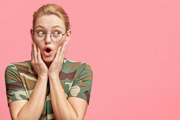 Verbaasd goed uitziende vrouw met geschokte blik, draagt een bril en vrijetijdskleding, heeft een blik op de lege kopie ruimte als poses tegen roze studio