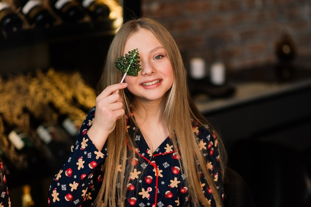 Verbaasd grappig kind likt snoep lolly thuis tijdens de wintervakantie
