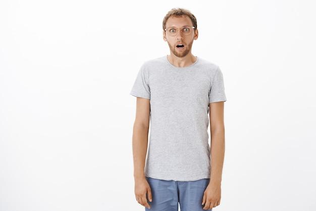 Verbaasd grappige aantrekkelijke blanke man met borstelharen in glazen kaak laten vallen staren schudde en verbaasd staande als marionet over witte muur