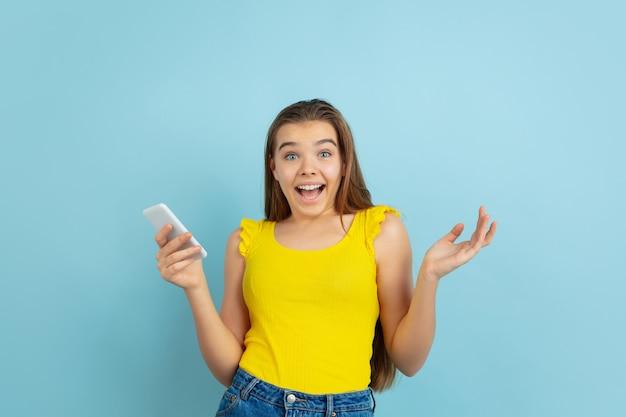 Verbaasd. het portret van het kaukasische tienermeisje dat op blauw wordt geïsoleerd