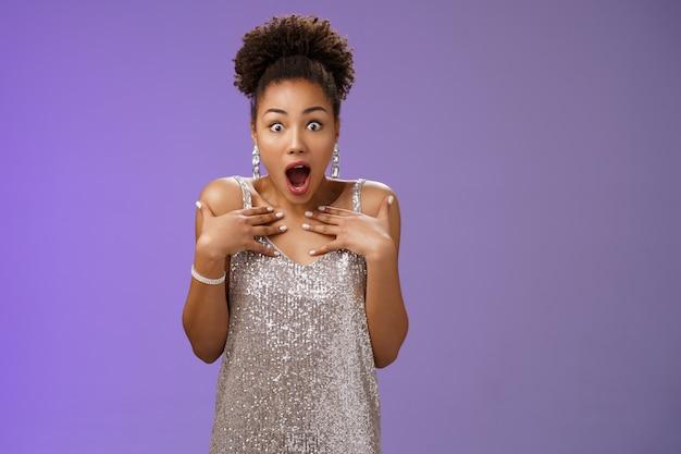 Verbaasd hijgend vroeg zich af geschokte aantrekkelijke afro-amerikaanse vrouw laat haar kaak vallen sprakeloos wijzend zelf onder de indruk kan niet geloven dat ze geluk heeft gehad met het winnen van de eerste plaats modelwedstrijd, blauwe achtergrond.