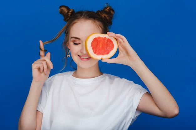 Verbaasd houdt het lachende meisje de grapefruit als oren vast. veganistische levensstijl. glimlachende vrouw, het eten concept. biologisch dieet, gewichtsverlies en gezonde voeding. smoothies en vers sap.