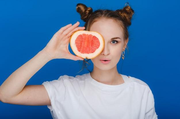 Verbaasd houdt het lachende meisje de grapefruit als oren vast Premium Foto