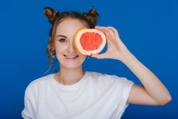 Verbaasd houdt het lachende meisje de grapefruit als oren vast