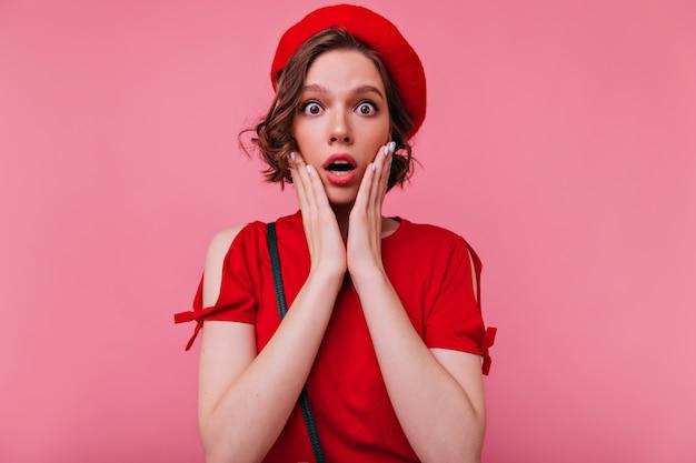 Verbaasd innemend meisje met bruin golvend haar op zoek. indoor portret van lieve franse dame verrast emoties te uiten.