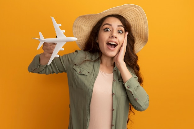 Verbaasd jong mooi meisje die olijfgroene t-shirt en hoed dragen die stuk speelgoed vliegtuig houden die hand op wang zetten die op gele muur wordt geïsoleerd