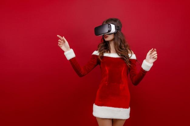 Verbaasd jong santameisje in kerstkleding die in hoofdtelefoon kijkt die handen opzij richt geïsoleerd op rode w...