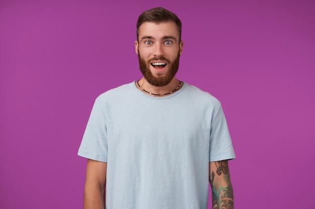Verbaasd jonge bebaarde brunette met trendy kapsel dragen blauwe t-shirt, met grote ogen en mond geopend, poseren op paars met handen naar beneden